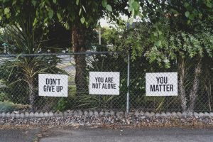 Signs on a fence telling people they are not alone, not to give up, and that they matter.