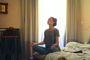 Woman meditating on an unmade bed.