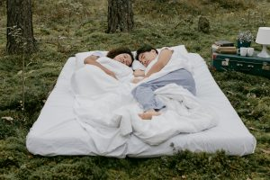 Couple dreaming on a bed in the grass